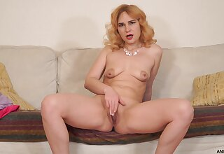 Adelis Shaman moans while pleasuring her pussy on the leather sofa