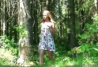 Amateur skeletal young chick squats down and pisses in the forest