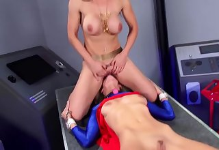 Gagged comme ci is wearing a superhero costume while her girlfriend is licking her wet pussy